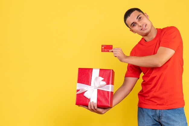 Front view of young man holding present and bank card on the yellow wall