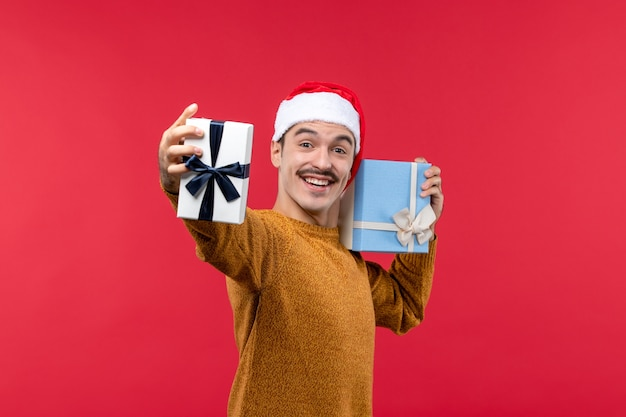 Front view of young man holding present boxes on red wall