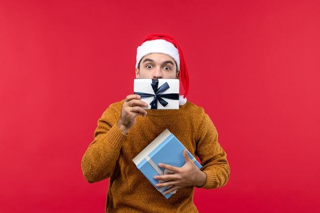 Vista frontale del giovane che tiene i regali sulla parete rossa