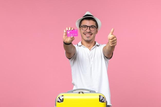 Vista frontale del giovane che tiene la carta di credito viola durante le vacanze estive sul muro rosa