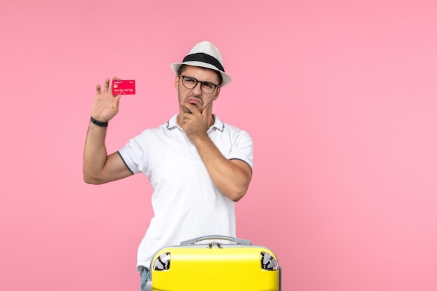 Front view of young man holding red bank card on light-pink wall