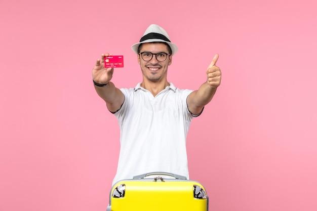 Vista frontale del giovane che tiene la carta di credito rossa sul muro rosa