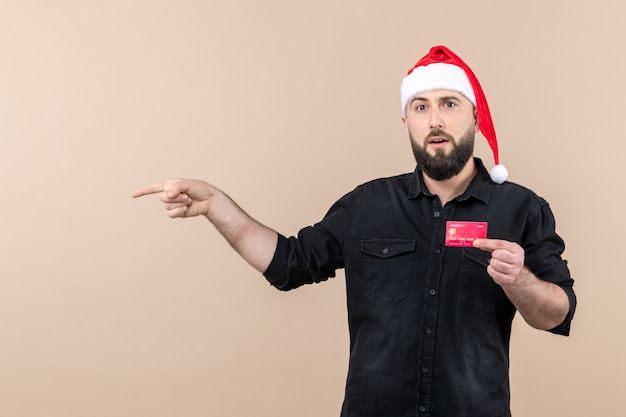 Front view of young man holding red bank card on pink wall