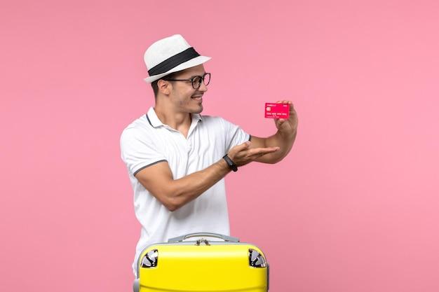 Vista frontale del giovane che tiene la carta di credito rossa durante le vacanze estive sul muro rosa chiaro