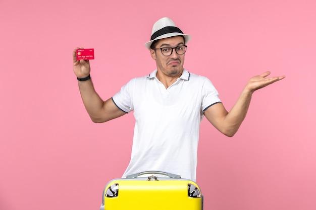 Vista frontale del giovane che tiene la carta di credito rossa in vacanza sul muro rosa