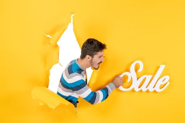 Vista frontale del giovane che tiene le lettere di vendita attraverso il foro a forma rotonda nel muro giallo