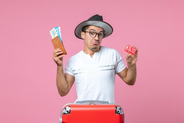 Vista frontale del giovane che tiene i biglietti e la carta bancaria sul muro rosa