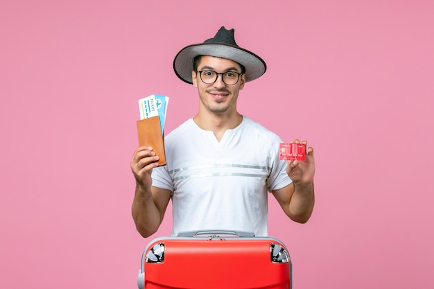 Front view of young man holding tickets and bank card on pink wall