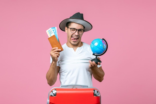 Front view of young man holding tickets and little globe on light-pink wall
