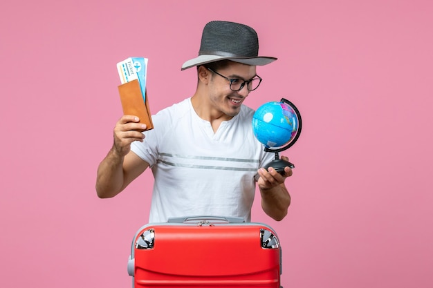 Front view of young man holding tickets and little globe on a pink wall