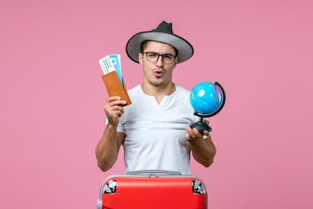 Front view of young man holding tickets and little globe on pink wall