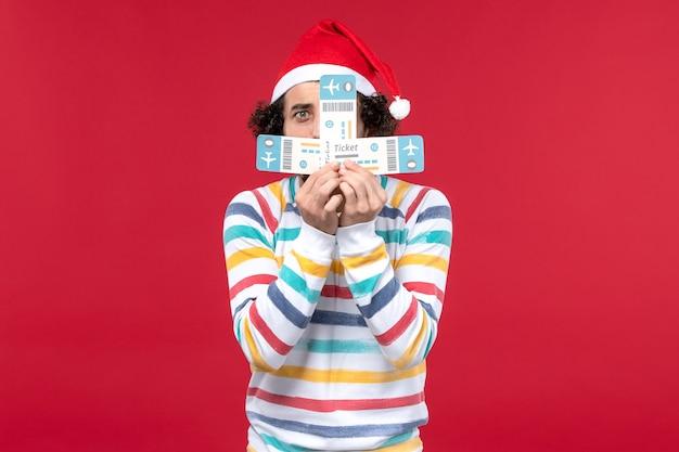 Вид спереди молодой человек, держащий билеты на красной стене самолета рейс новый год красный