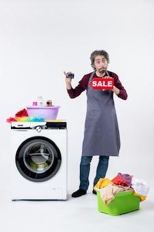 Вид спереди молодой человек, держащий карточку и знак продажи, стоящий возле корзины для белья стиральной машины на белой стене