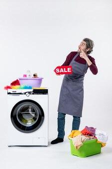 Giovane di vista frontale che sostiene il segno di vendita che sta vicino ad un cesto della biancheria della lavatrice sulla parete bianca