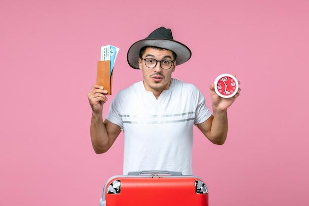 Vista frontale del giovane che tiene i biglietti per le vacanze e l'orologio sulla parete rosa