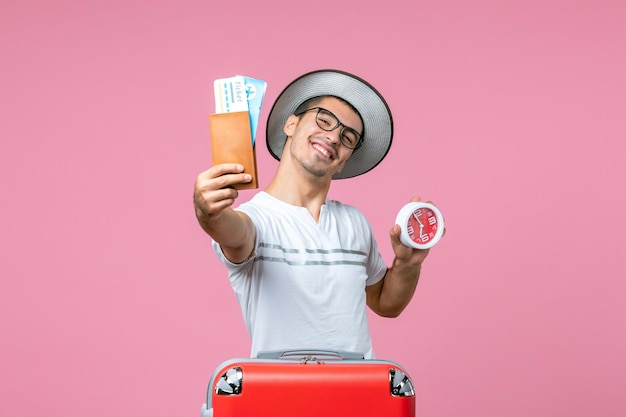 Front view of young man holding vacation tickets and clock on pink wall