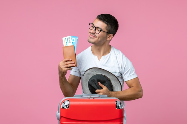 Front view of young man holding vacation tickets and his hat on a pink wall