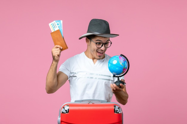 Front view of young man holding vacation tickets and little globe on light pink wall