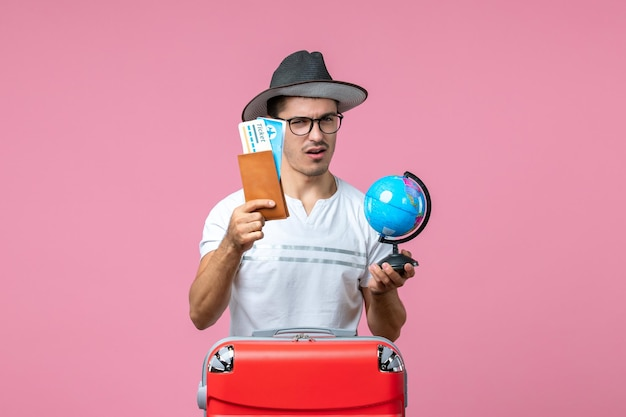 Front view of young man holding vacation tickets and little globe on pink wall