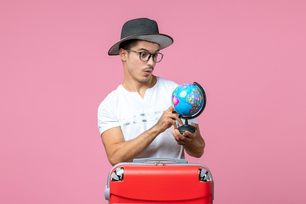 Front view of young man holding vacation tickets and little globe on the pink wall