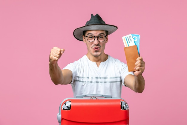 Front view of young man holding vacation tickets on pink wall