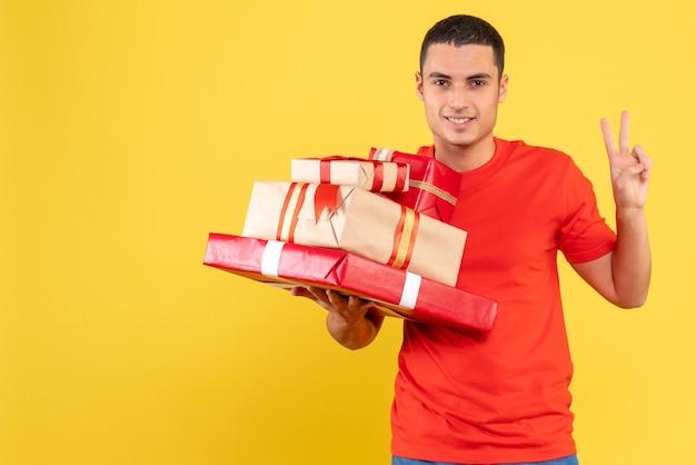 Vista frontale del giovane che tiene i regali di natale sulla parete gialla