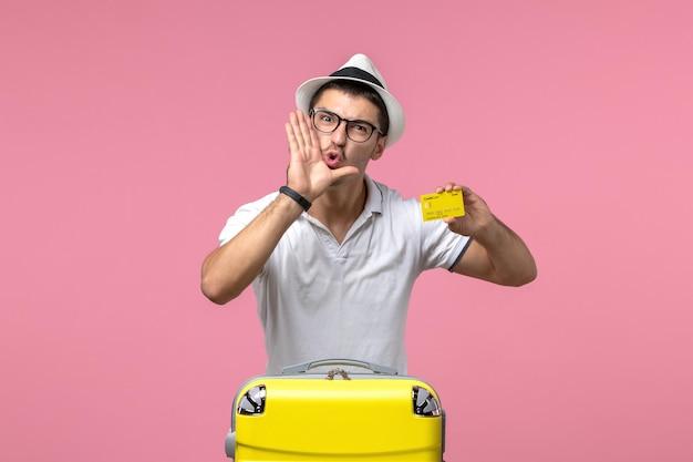Vista frontale del giovane che tiene la carta di credito gialla e urla su un muro rosa