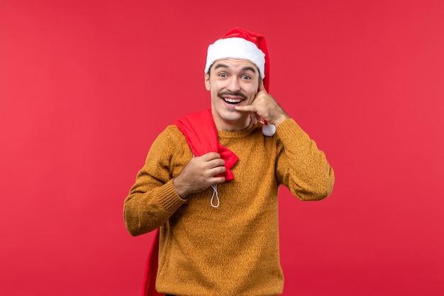 Vista frontale del giovane che imita la telefonata sulla parete rossa