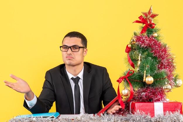 그의 손에 크리스마스 트리와 선물을 여는 테이블에 앉아 소송에서 전면보기 젊은 남자