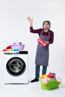 앞치마를 입은 젊은 남자가 흰 벽에 있는 세탁기 근처에 손을 올리는 판매 표지판을 들고 있다