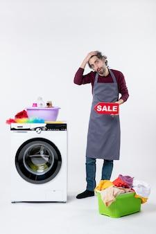 Вид спереди молодой человек в фартуке, держащий знак продажи, стоящий возле корзины для белья стиральной машины на белой изолированной стене