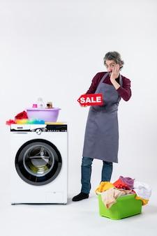 Вид спереди молодой человек в фартуке, держащий знак продажи, стоящий возле корзины для белья стиральной машины на белой стене