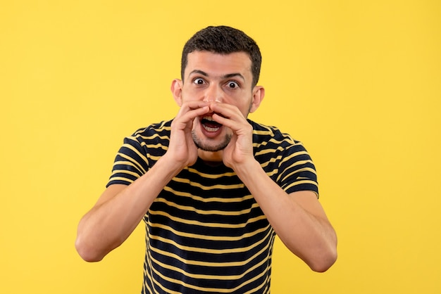 黄色の孤立した背景で誰かを呼び出す黒と白の縞模様のtシャツの正面図の若い男