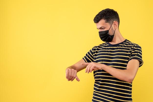黄色の背景の時計の時間をチェックする黒と白の縞模様のtシャツの正面図若い男