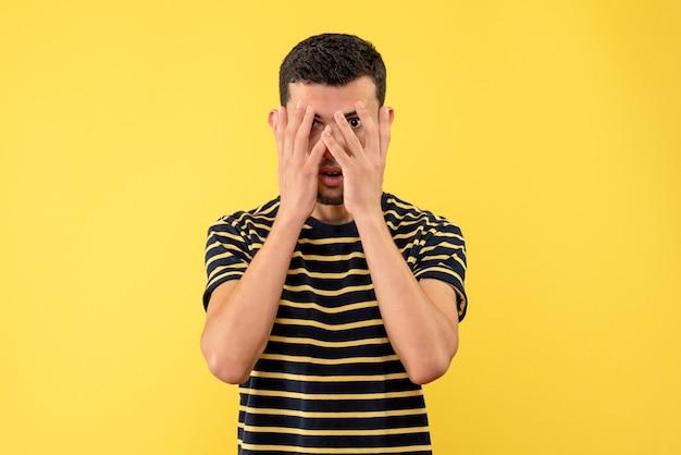 격리 된 노란색 배경에 손으로 얼굴을 덮고 검은 색과 흰색 줄무늬 티셔츠에 전면보기 젊은 남자