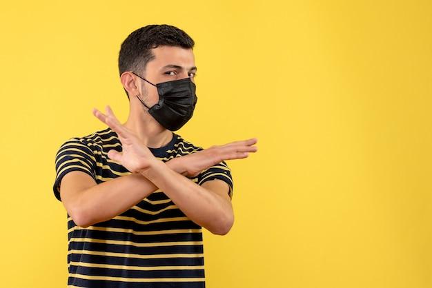 검은 색과 흰색 줄무늬 티셔츠 횡단 손 노란색 배경에서 전면보기 젊은 남자