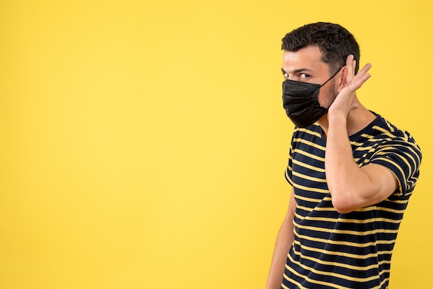 黄色の背景で何かを聞いている黒と白の縞模様のtシャツの正面図の若い男