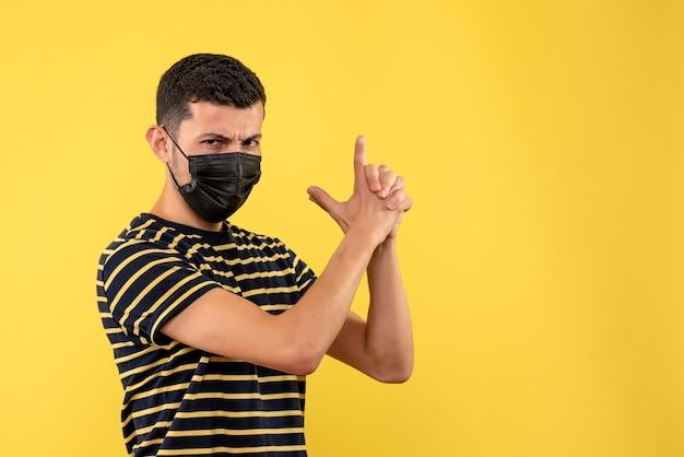 노란색 배경에 손가락 총을 만드는 흑백 줄무늬 티셔츠에 전면보기 젊은 남자