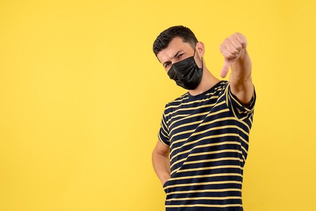 Вид спереди молодой человек в черно-белой полосатой футболке делает большой палец вниз знак на желтом фоне