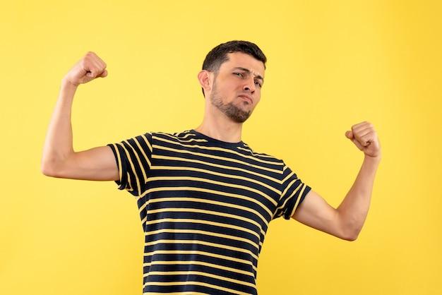 격리 된 노란색 배경에 승리 제스처를 만드는 흑백 줄무늬 티셔츠에 전면보기 젊은 남자