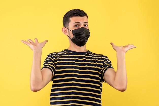 검은 색과 흰색 줄무늬 티셔츠 여는 손에 노란색 배경 전면보기 젊은 남자