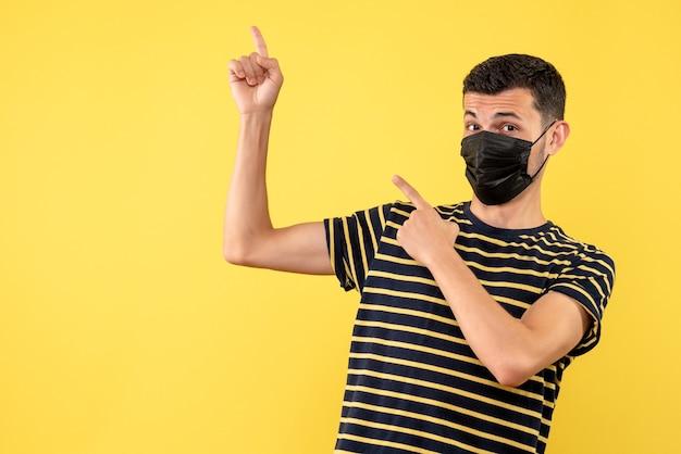 Вид спереди молодой человек в черно-белой полосатой футболке, указывая на спину на желтом фоне