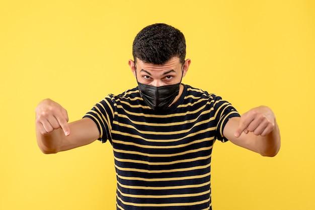 Вид спереди молодой человек в черно-белой полосатой футболке, указывающий на пол на желтом изолированном фоне