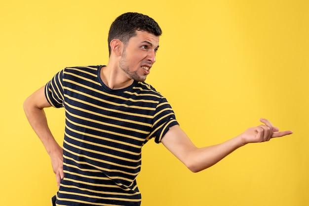 Вид спереди молодой человек в черно-белой полосатой футболке, положив руку на талию на желтом изолированном фоне