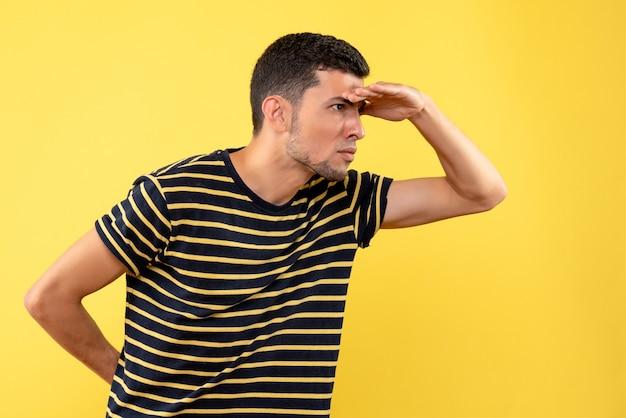 Вид спереди молодой человек в черно-белой полосатой футболке, положив руку ко лбу на желтом изолированном фоне