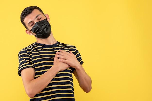 黄色の孤立した背景に心に手を置く黒と白の縞模様のtシャツの正面図若い男