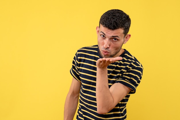 Вид спереди молодой человек в черно-белой полосатой футболке, отправляющий поцелуй на желтом изолированном фоне