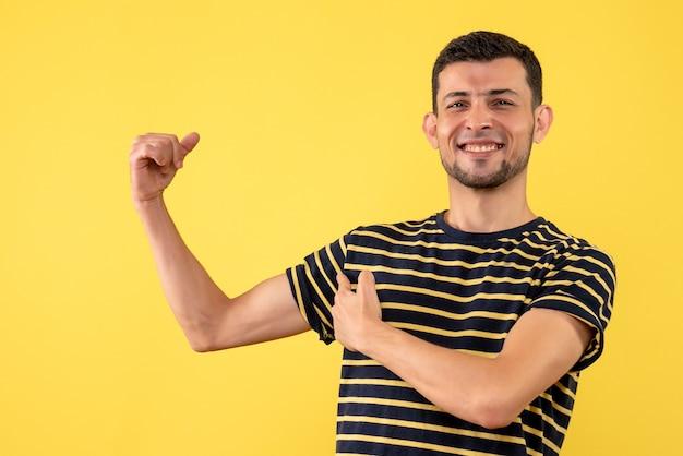 Вид спереди молодой человек в черно-белой полосатой футболке, показывающий мышцы руки на желтом изолированном фоне