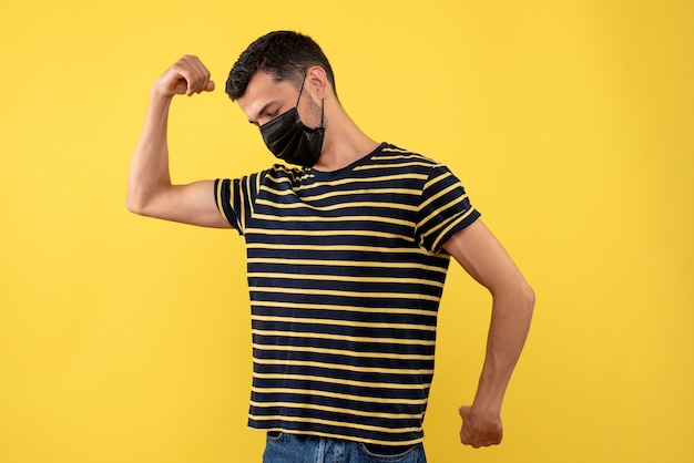 Молодой человек в черно-белой полосатой футболке, вид спереди, показывает мышцы на желтом фоне