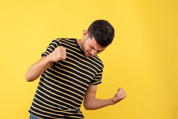 黄色の孤立した背景に勝利のジェスチャーを示す黒と白の縞模様のtシャツの正面図の若い男